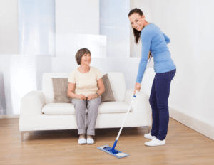 caretaker cleaning the floor with a mop while a senior woman sitting on the sofa